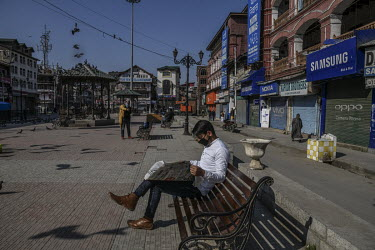 A man sits on a bench reading a newspaper outside a closed market in Lal Chowk. The first positive case of which was identified in the Khaniyar area the previous night leading the local government to...