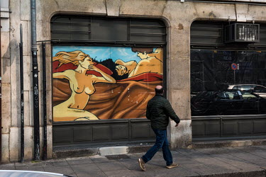 A man looks at an erotic painting decorating the window of a place of prostitution in the red light district. All prostitution has been banned as part of Switzerland's lockdown measures in response to...