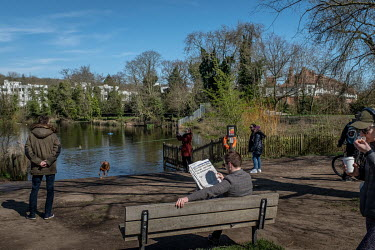 People relax in the spring sunshine by the dog pond on Hampstead Heath, a large area of park and lakes in north London. People ignoring the government's advice on social distancing led to a lockdown b...