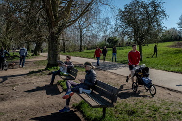 People relax in the spring sunshine in Hampstead Heath, a large area of park and lakes in north London. People ignoring the government's advice on social distancing led to a lockdown being implemented...