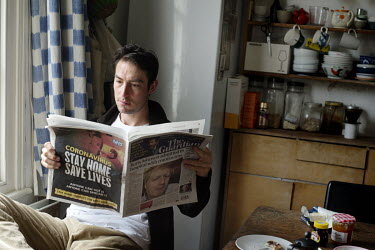 Life in a time of coronavirus. Louis reads the Guardian with an advert on the back page telling people to stay home and a photo of Boris Johnson on the front with news that he has been admitted to hos...