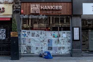 A homeless person's sleeping bag outside a restaurant where the windows have been covered with newspapers. Shops and businesses throughout the country have been closed due to the coronavirus pandemic.