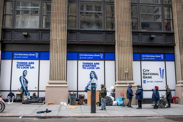 A homeless people's encampment on a pavement outside a bank street in New York City.