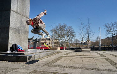 Robert, wearing a homemade face mask, rides a skateboard at the memorial column to the victims of communism. Since 18 March 2020 face coverings are mandatory in all public spaces across the country.