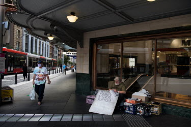 A man begging with a sign that reads: 'Needing family medical support', in the popular shopping area near the Queen Victorian Building, on George Street.