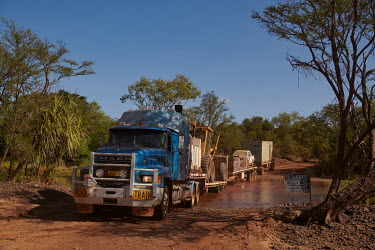 The vehicle drives through a muddy creek, past a sign warning of crocodiles, on the Gibb River Road, as Nick and Joanna Atkins' road train makes its way from Kununurra to Kalumburu.