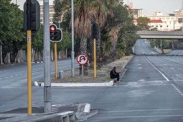 A homeless man, waiting to beg from cars stopped at the traffic lights, sits by an empty highway in central Cape Town during the coronavirus lockdown.