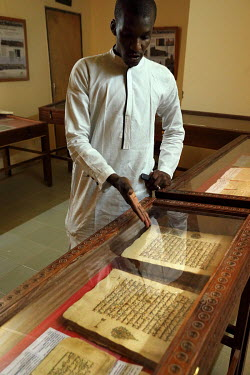 El Hadj Sissi, the son of the Imam of the main mosque in the city (the Djiengaraiber mosque), points to a display of ancient manuscripts that they managed to save from destruction by Islamist insurgen...
