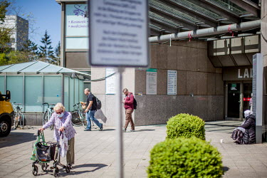 A warning sign explaining social distancing rules, a Bosnian woman begging on the pavement and an elderly woman wearing a face mask and using a walker (rollator).