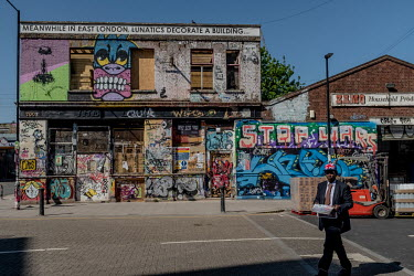 A man walks past derelict building covered in graffiti in Hackney Wick, east London.