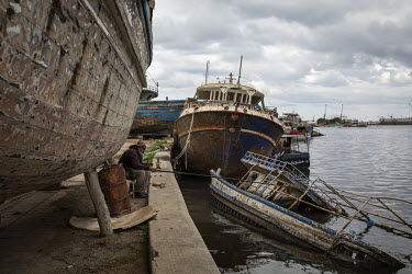 A man fishing, amidst decommissioned boats, in the harbour near Benghazi's fish market. The east of Libya, particularly the regional capital of Benghazi, has endured severe hardship through years of c...
