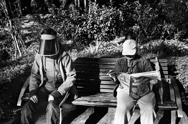 A woman wearing a face visor sitting on a bench in Victoria Park.