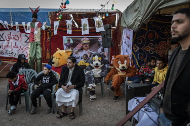 People, including some dressed in novelty costumes, attend a rally in support of the Libyan National Army and General Haftar in Revolution Square.