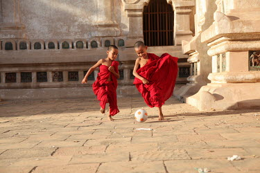 Two novice monks play football at a pagoda.