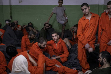 American ISIS member, Abdelhamid Al-Madioum (centre), sits amongst his fellow inmates in the crowded cell they share at a prison run by Kurdish forces in northeast Syria.