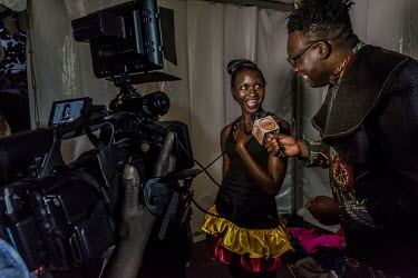 A candidate in the Y+ beauty contest is interviewed by Urban TV, a fashionable Ugandan television channel, backstage at the hotel where it is being held. The Y+ beauty contest is national competition...