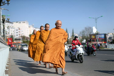 Monks walking down the street collecting alms.