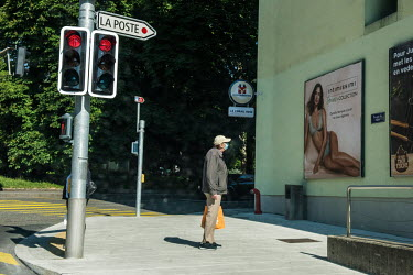 A man wearing a face mask looks at an adevertising poster featuring a woman in underwear.
