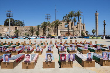 Replica coffins with photographs attached of martyrs of the Libyan revolution, displayed on Martyr's Square. In the background is the National Museum, situated in the Assaraya Alhamra or Red Castle.