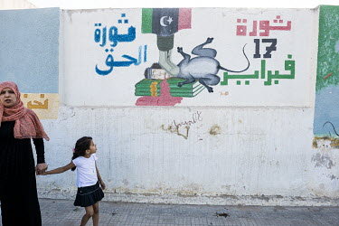 A mother and child pass by a mural depicting Colonel Muammar Gaddafi as a rat, being trampled underfoot while he lies on top of copies of the Green Book. 17 February refers to the Day of Rage, the sta...