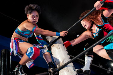 Kaho Kobayashi (left) and her opponent Hiroyo Matsumoto fight on the ropes during their bout at an Oz Academy Women's Pro-Wrestling competition held at the Shinjuku Face arena.