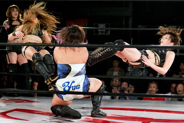 A tag team perform a flying manoeuvre during a bout at an Oz Academy Women's Pro-Wrestling competition held at the Shinjuku Face arena.