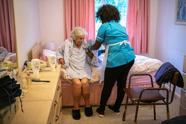 Mabinty Kolifa-Kargbo, a part-time care worker, helps an elderly woman get ready for bed during the coronavirus lockdown.