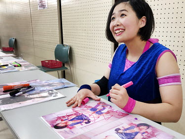 Popular female wrestler Mayumi Mirai signs a promotional photograph for a fan during a paid for photo and autograph session during a women's wrestling competition held in the Green Hall in the Itabash...
