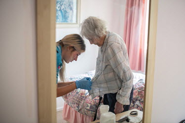 Jadesmith Taylor, a care worker, helps an elderly woman who suffers with dementia get ready for bed during the coronavirus lockdown.