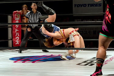 Yu (blue) performs a spectacular move on her opponent during a bout at a women's wrestling competition held at the Shin-Kiba 1st Ring in the Shinkiba district.