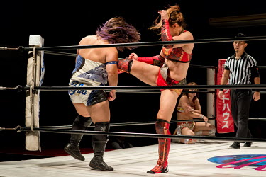 Yu (blue) receives a kick from her opponent during a bout at a women's wrestling competition held at the Shin-Kiba 1st Ring in the Shinkiba district.
