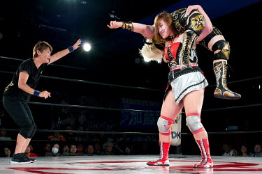 Women wrestlers fight during a bout at an Oz Academy Women's Pro-Wrestling competition held at the Shinjuku Face arena.
