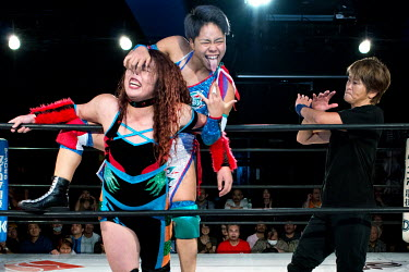 Kaho Kobayashi makes a grimace at the audience as she makes her opponent Hiroyo Matsumoto suffer during their bout at an Oz Academy Women's Pro-Wrestling competition held at the Shinjuku Face arena.