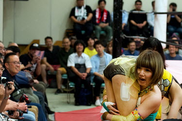 Much to the delight of the audience, a wrestler carries her opponent outside the ring during a women's wrestling competition held in the Green Hall in the Itabashi district.