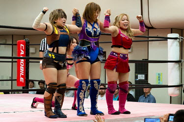 A female wrestling team salute the audience during a women's wrestling competition held in the Green Hall in the Itabashi district.