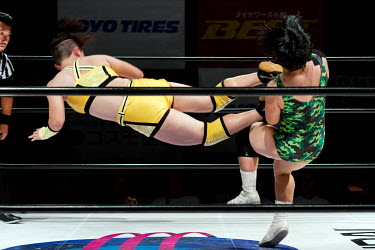 A wrestler performs a flying drop kick on her opponent during a women's wrestling competition held at the Shin-Kiba 1st Ring in the Shinkiba district.