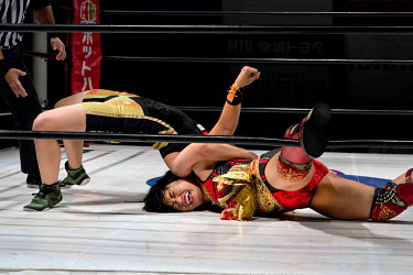 Meiko Satomura (from the Sendai Girls female wrestling promotion), in red, is forced to the canvas during a women's wrestling competition held at the Shin-Kiba 1st Ring in the Shinkiba district.