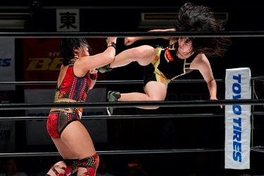 Manami (from the Sendai Girls female wrestlering promotion) performs a flying drop kick on fellow Sendai Girl, Meiko Satomura during a women's wrestling competition held at the Shin-Kiba 1st Ring in t...