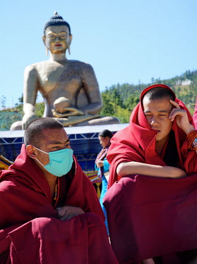 Monks sitting near the Great Buddha Dordenma.