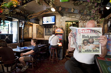 A man reading The Sun newspaper in the 'The Angry Friar', a 'British pub' in Gibraltar.