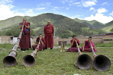 Buddhist monks practice the sounding of the dungchen (a ritual horn or trumpet) at Labrang Monastery in the ethnic Tibetan village of Xiahe.