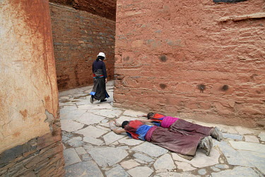 A pair of Buddhist monks on pilgrimage prostrate themselves while performing a Kora (Circumambulation) around the Labrang Monastery in the ethnic Tibetan village of Xiahe.