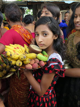 A Hindu girl carries a plate of fruits at a religious ceremony in the village of Govinda Pur.