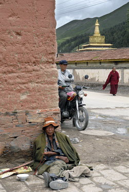 A beggar, a motorbike and a Buddhist monk near the Labrang Monastery in the ethnic Tibetan village of Xiahe.