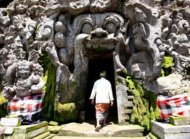 A man enters the Goa Gajah sanctuary, a temple hewn from rock.