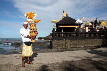 A pilgrim holds his offering as he makes his way to the Pura Tanah Lot temple.
