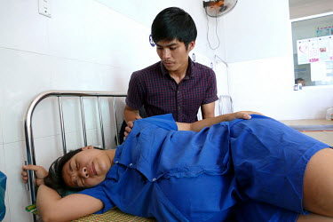 Tran Kim Vinh tries to comfort his wife Nguyen Thi Thu Ngan as she suffers labour pain while waiting to give birth in the Department of Obstetrics & Gynaecology at Quang Nam General Hospital.