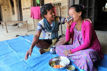 Sujta (26), who is pregnant, eats a nutritious meal while her husband Shiva (28) sits with her.
