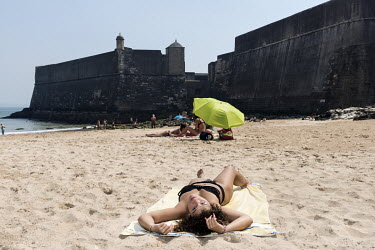 A woman sunbathing on Praia da Torre beach whose western edge is bound by the massive Santo Juliao Bara fort.