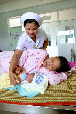 A nurse checks Nguyen Thi Dieu (20) and her newborn boy as they are resting on a ward in the Department of Obstetrics & Gynecology at Quang Nam General Hospital.